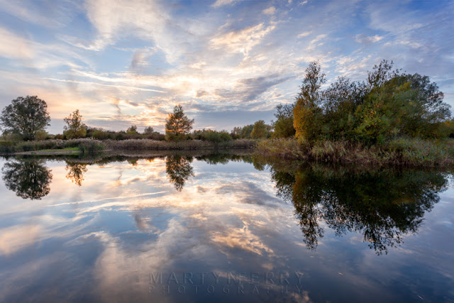 Clouds reflect in the river at Ouse Fens in Cambridgeshire