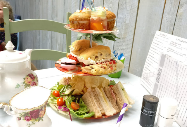 a 3 tiered stand with sandwiches and crisps, scones and meringues, and carrot cake buns and mini jars of trifle