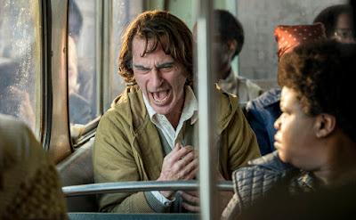 Joaquin Phoenix laughs loudly on a crowded bus in the movie Joker, directed by Todd Phillips