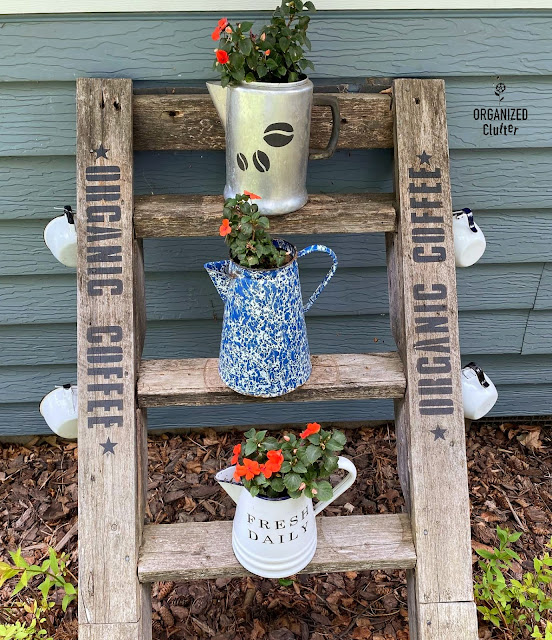 Photo of a ladder decorated with an Organic Coffee stencil, coffeepots with impatiens, and coffee cups