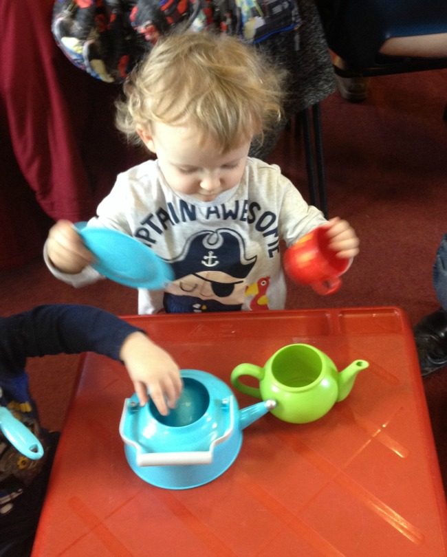 Two toddlers playing with cups and teapots