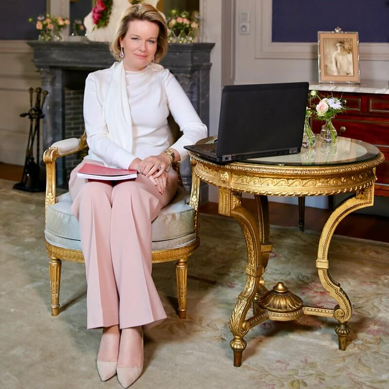 Queen Mathilde wore a white silk bow blouse by Natan, and pink trousers by Armani. Pink diamond earrings