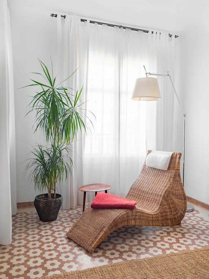 Rincón de lectura con paredes blancas y suelo hidrúalico