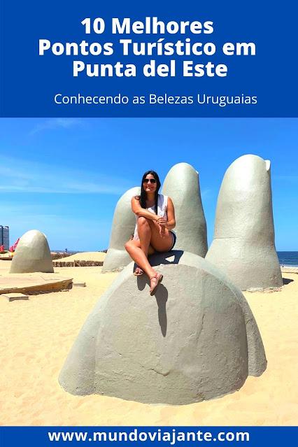 mulher em cima da escultura de los dedos em punta del este