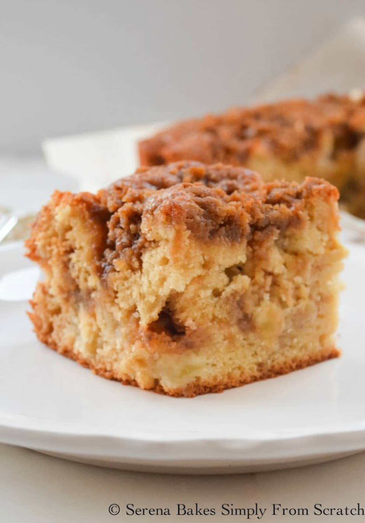 A slice of Apple Coffee Cake filled with Granny Smith Apples and a Brown Sugar Cinnamon Crumb and Swirl on a white plate.