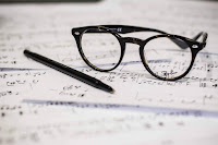Pen and glasses on a musical notebook