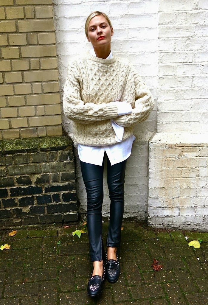 Pandora Skyes in a Cable Knit Sweater, White Shirt, Leather Pants, and Studded Loafers
