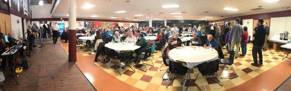 crowd sitting in room eating dinner