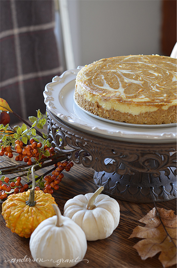 Pumpkin cheesecake on cake stand with pumpkins and gourds