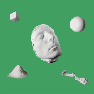 Plaster cast of Bernholz's face surrounded by a cube, sphere, pile of plaster dust and a tube of paste. White on green.