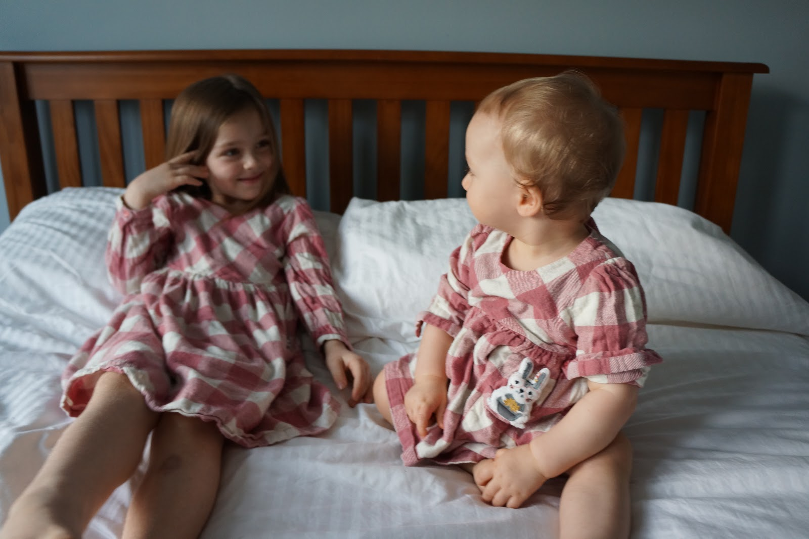 baby and sister in matching outfits looking at each other