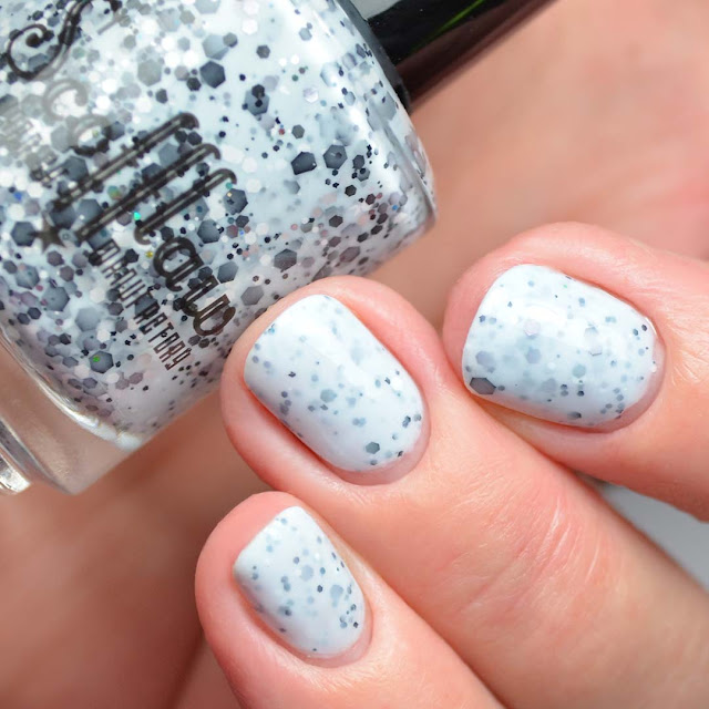 light blue nail polish with black glitter three finger swatch