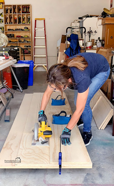 Cristina Garay using Dewalt circular saw and straight edge to cut ply doors