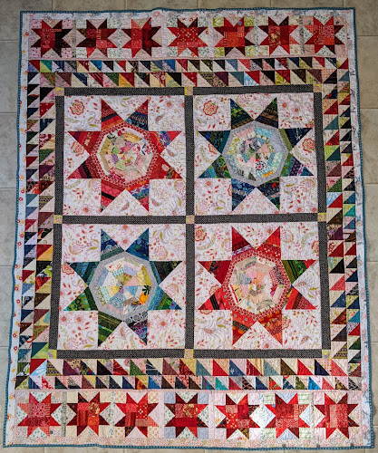 The center of this scrap quilt is four LeMoyne stars in red or blue surrounded by two rows of HSTs with a row of red Sawtooth Stars at the top and bottom of the quilt.