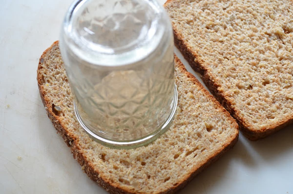 A slice of bread with a large canning jar being pressed into bread.