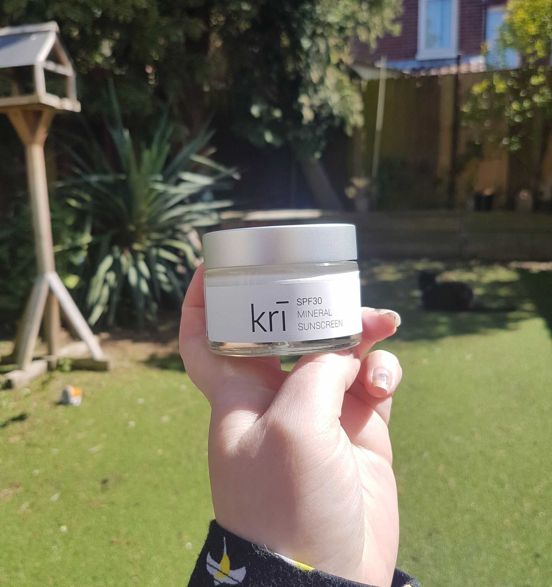 glass jar of reef safe SPF30 mineral sunscreen from Kri Skincare held up in a hand outside in front of a bird table and trees