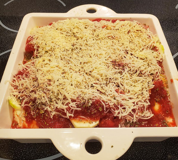 this is a zucchini ricotta casserole with shredded mozzarella cheese on top before its baked with tomato sauce