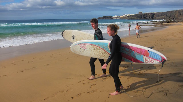 two surfers on the beach holding mini mal surfboards