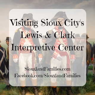 """in background, animatronic figures of Meriweather Lewis and William Clark stand in front of a painted mural depicting other members of the Corps of Discovery. In front, the words """"visiting Sioux City's Lewis and Clark Interpretive Center"""" and """"SiouxlandFamilies.com Facebook.com/SiouxlandFamilies"""""""