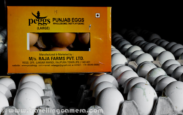 During Christmas vacations I visited Rajpura (a town in Punjab, India) with my friend, who was visiting one of his clients for some official purpose. We exactly went to a company called 'Punjab Eggs', which is one of the decent Egg producers of Punjab with main focus on nutrition. Here we are not going to share the technicalities involved, but a Photo Journey to a  Punjab Eggs Farm. Let's check it out.. It was Monday, when I was in Chadigarh and my friend called me to get ready for Rajpura, which is a relatively small town in Punjab. It took approximately 1 Hr to reach the place. We had to meet Mr. Mohit Raja, which is one of the partner in Punjab Eggs. Naresh(my friend) had official meeting with Mohit, who is also managing some other companies in Rajpura RegionPunjab Eggs is a brand of Raja Farms and one of the good quality product in North India, (as I got to know from this visit...) There are different types of eggs distributed by Peggs, depending upon the nutrition value. Different packing are used after automatic identification of different types of eggs.Cleanness and discipline is one of the main demand of such poltery farms. Cars are not allowed to come inside the campus. In worst case, if any vehicle need to come inside this huge farm, there is a track full of water, so that tyres and lower part of the vehicle is cleaned before it actually enters that campus. If someone comes inside, some solution is sprayed on shoes.Above photograph shows the preparations one need to do, before entering into the space where hens are kept under controlled temperature. A mask, cap & shoe cover etc.Here is the first view after entering into the poultry farm and this whole setup was constructed in consultation with an Europian company. Things like, space (width, height, length), Air conditioning systems, alignment of exhaust fan, unit for automatically collection eggs, cleanness of  each compartment, machines for providing feeds etc were designed in such a way that everything can be controlled through single unit on one of the corners of this poultry farmThere were different alleys with 4 storey units on both side. Each alley had hens of different types. There were two containers in front of each row - One for providing feed and other for collecting Eggs. Eggs were automatically collected at a central place, where each of them is weighted and packed accordinglyHere is a external view of Punjab Eggs unit of Raja Farms Co @ Rajpura, Punjab, IndiaMany folks prefer yellow-cover eggs and some sections of this poultry farm were having hens of a particular species. As an egg hits the region you see in this photograph, egg count of the unit goes up and can be checked exact count anytime in the software installed on conputer, which is connected to the main control unitIt was lunch time when we reached the poultry farm and all of them were busy in having their regular feed. Temperature inside was unbearable for us and whole environment was dusty due to feed distribution process, which is again handled automatically. But someone needs to refill the main containerHere exactly is feed distribution unit, which keep moving between the compartments and provide appropriate amount of feed at regular intervalsHens on right side and waiting for their turn and feed-machine of their side is still on other end of the hallExhaust fan installed on back-side of the poultry farm. each unit can be controlled separately and used  to make sure that their is proper air ventilation, along with appropriate temperature inside the poultry farMan standing in other room, where all eggs come through a rolling path. At the end of this moving path, there was a controller to weight each egg and move into appropriate sections. After this all eggs are collected and packed accordingly. There is a particular type of egg, which is marked for 'Peggs' logo...A photograph of warehouse, where some of the egg containers were lying around a corner.All special types of eggs are packed in this kind of packs with proper marking on theOthers are served in standard treys.To summarize this PHOTO JOURNEY - A Visit to fully automated Poultry Farm with Naresh and Mohit Raja. Punjab Eggs at Rajpura, Punjab, India takes care of hygiene and nutrition in their products. Overall it was a great experience to see this kind of setups in India.