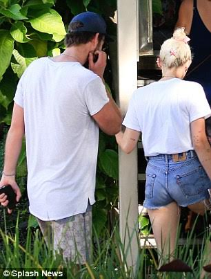 Miley Cyrus wears revealing nude colored top as she joins