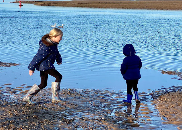 2 sisters splashing away on the edge of the sea in coats and wellies