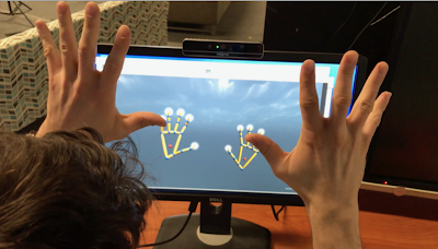 Image of person with hands in the air in front of a video display showing stick-model hand images.