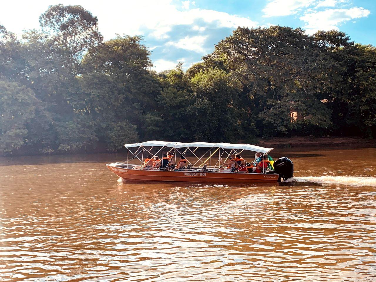 barco laranja a motor com turistas a bordo