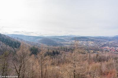 """Widok z platformy: z lewej na linii horyzontu Stożek Wielki; nieco z prawej masyw Dzikowca z wyciętym białym """"pasem"""" pod infrastrukturę narciarską"""