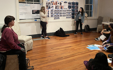 Cheryl is seated at left. Two students are standing in front of different designs and seen talking through different ideas. Other students are seated on the wooden floor. Many printouts are taped to the wall.