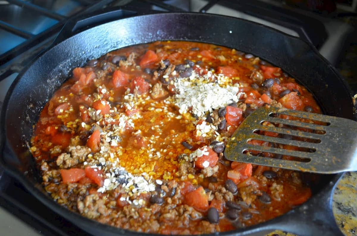 Cook ground beef, canned tomatoes, tomato paste, black beans, oatmeal and water in a cast iron skillet.