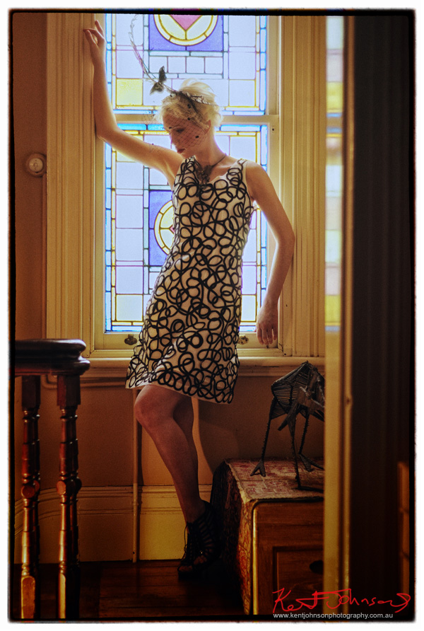 Full length shot of a fashion model before a stained glass window in a Victorian house. Photographed by Kent Johnson, Sydney, Australia.