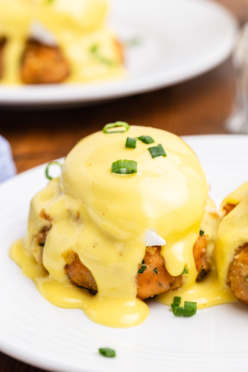 Close up photo of Keto Salmon Eggs Benedict on a white plate with chives on top.