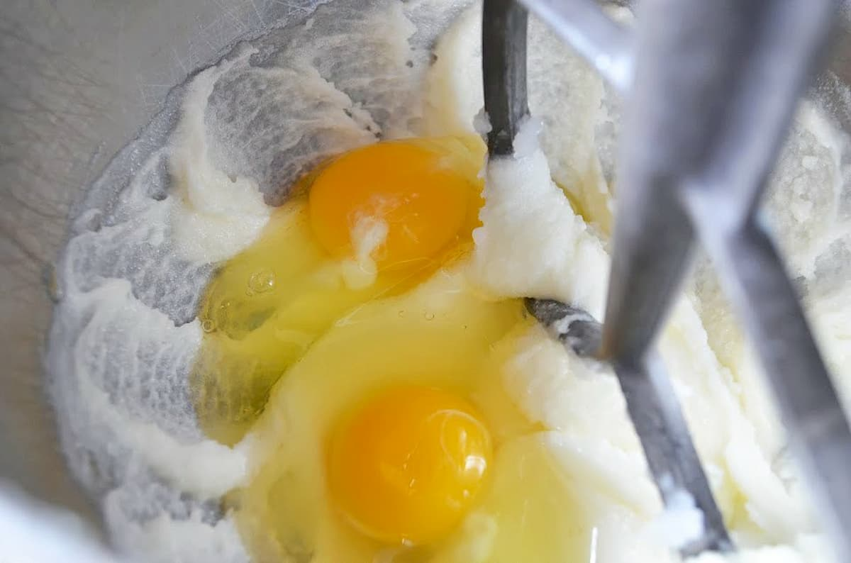 Eggs added to creamed coconut, butter, sugar mixture in a mixing bowl.