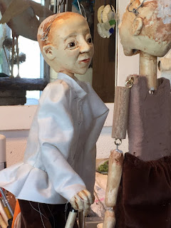 two Reflection Dancer puppets partly dresses, looking at each other in Corina Duyn's studio