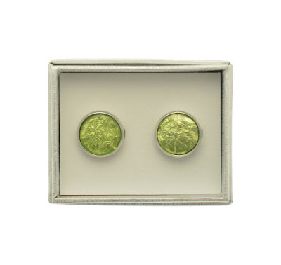 White box resting on a white surface with light  green coloured round Cufflinks inside