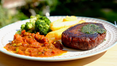 Vegan steak on a plate with chips and broccoli