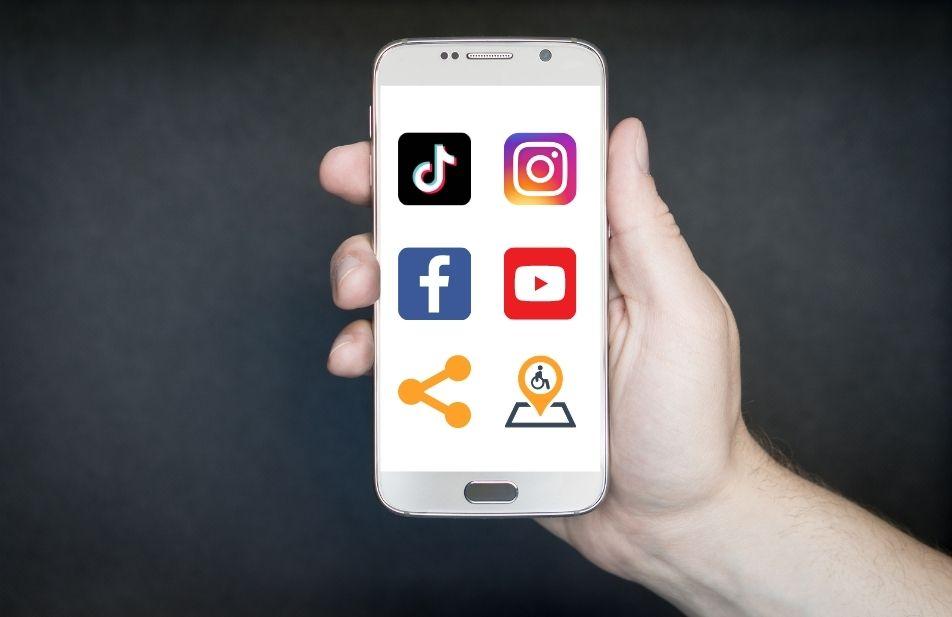 A imagem mostra uma mão segurando um celular, na tela do celular está as principais redes sociais com o ícone  de compartilhamento e logomarga do território deficiente