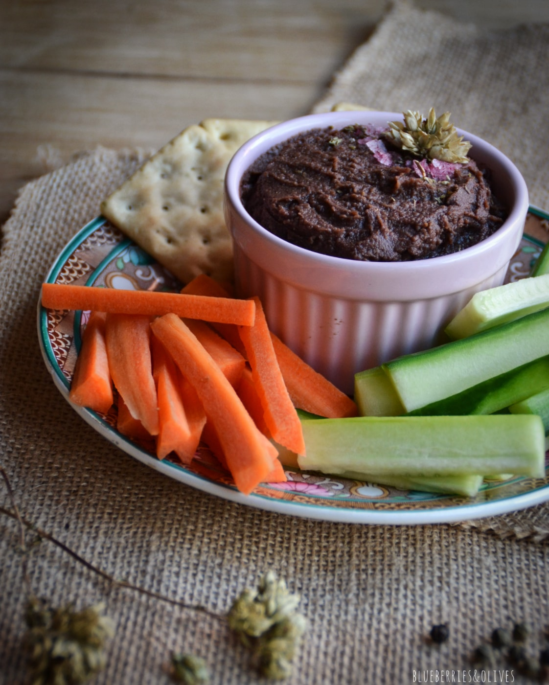 vegetable spread in pink bowl with crudités and a wood table with old tablecloth