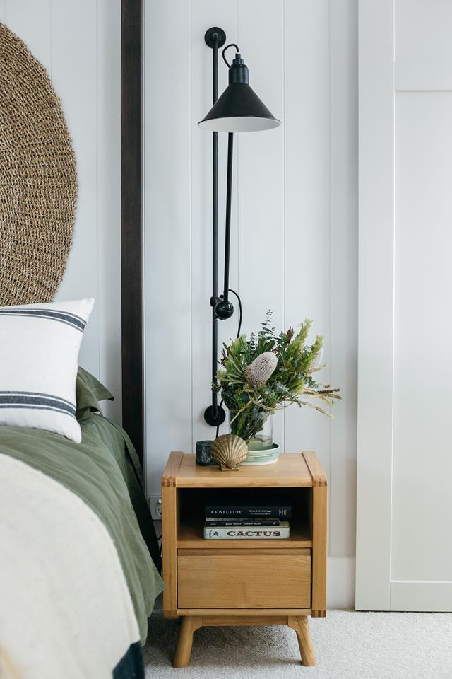 Nightstand and wall sconce in the main bedroom