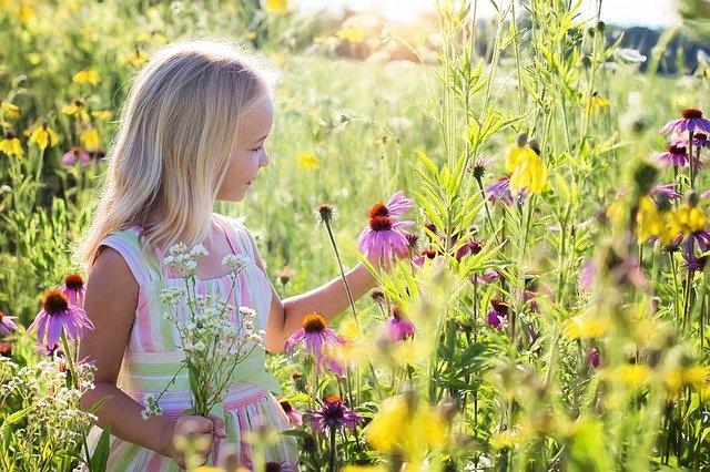 Gadis kecil yang memandangi bunga yang indah