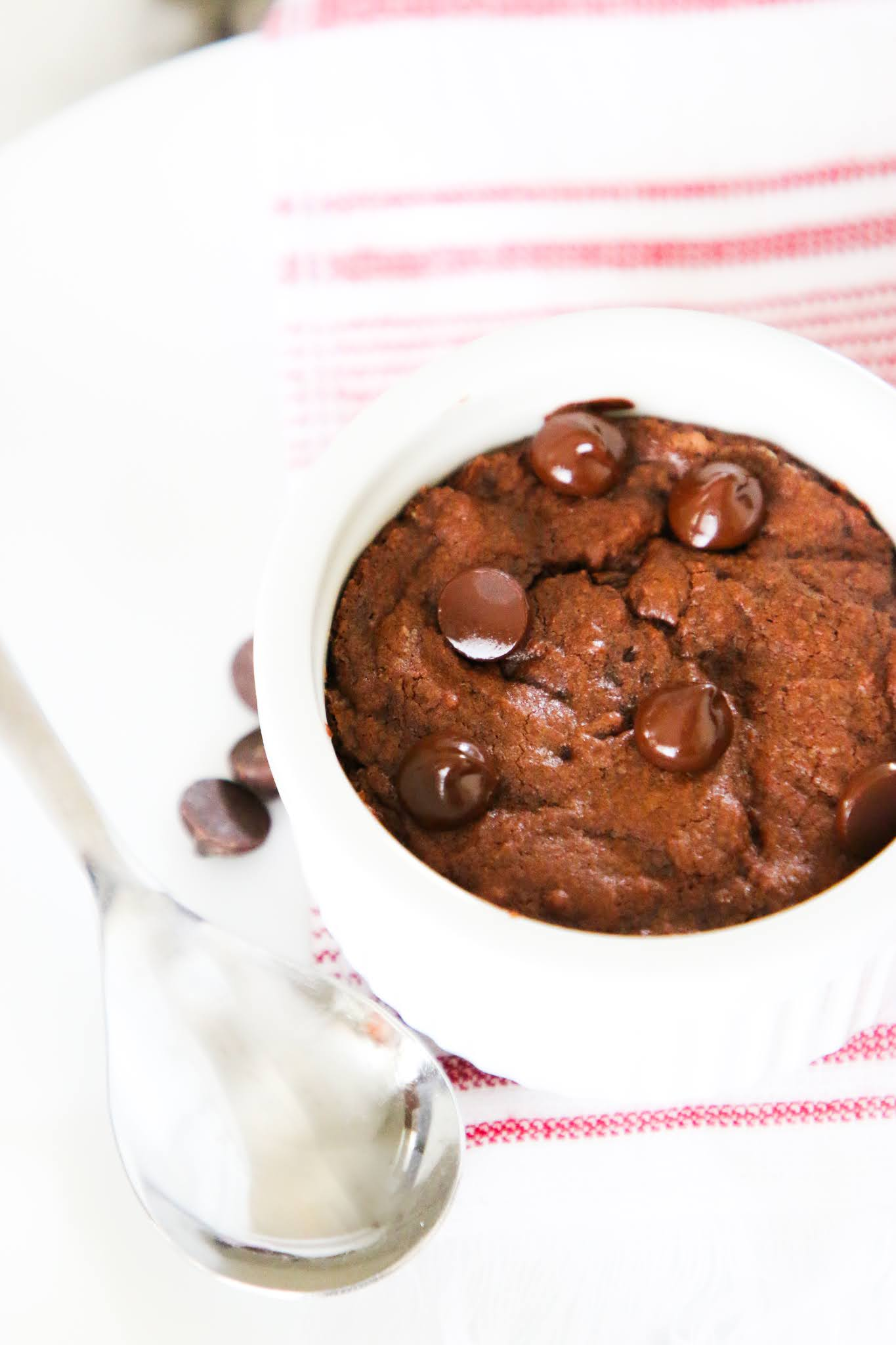 Brownie baked in a small white ramekin on top of a red dish towel placed on a white plate with scattered chocolate chips on a white marble table.