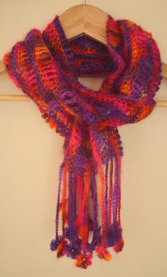 Floral Fantasy scarf designed by Jodiebodie - The wavy-striped scarf in purple/orange and pinks is hanging on a coathanger as if it were around a neck. The floral motifs in the fringe hang at different lengths to create a pretty collection of flowers.
