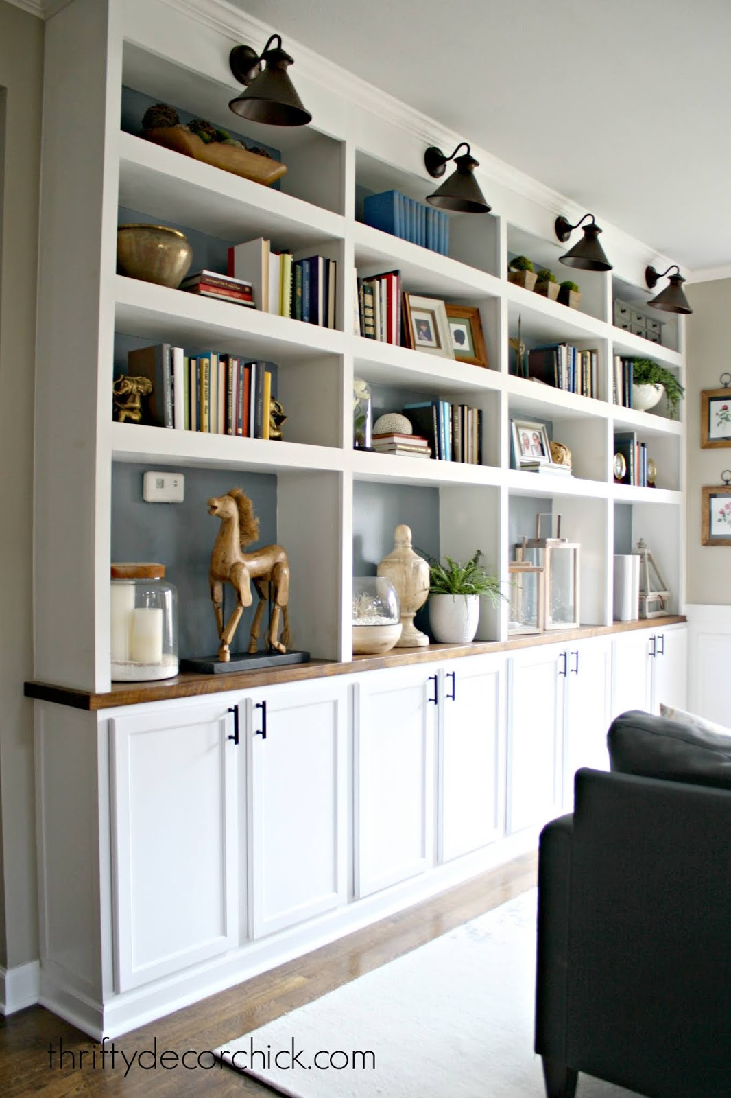 huge wall of DIY bookshelves with kitchen cabinets