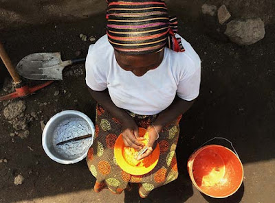 South African woman grinding corn into cornmeal for dinner