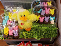 Brightly colored marshmallow peep bunnies dipped halfway in chocolate are packaged with cellophane in trios and sit in green paper grass next to a plush yellow duck at Palmers Candy in Sioux City