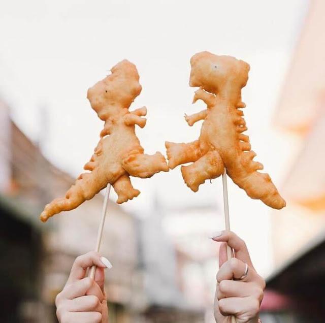 """Món bánh rán khủng long ngay từ khi xuất hiện đã được các bạn trẻ tích cực """"săn lùng"""" để thưởng thức. Bánh rán tưởng chừng như một món ăn bình dân, quen thuộc, nay lại được các đầu bếp tạo hình thành những con vật ngộ nghĩnh. Ngoài hình khủng long, bánh còn có bánh hình voi, rồng, cá sấu; được rán khi thực khách đến nên luôn nóng hổi và giữ được độ giòn vừa miệng."""