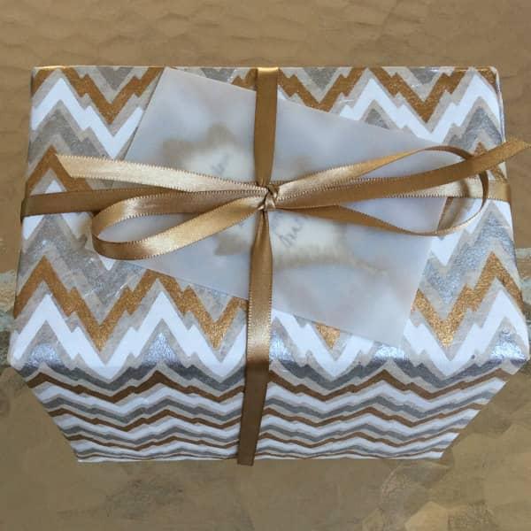 huwelijkscadeau verpakt in zilver, goud en wit zigzagdesignpapier met gouden lint en doorschijnende perkamentenvelop met bladcadeaubon