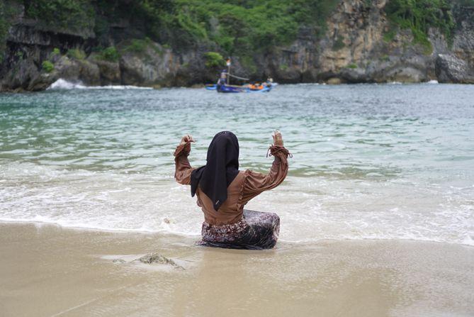 Wisatawan bermain air di Pantai Gesing
