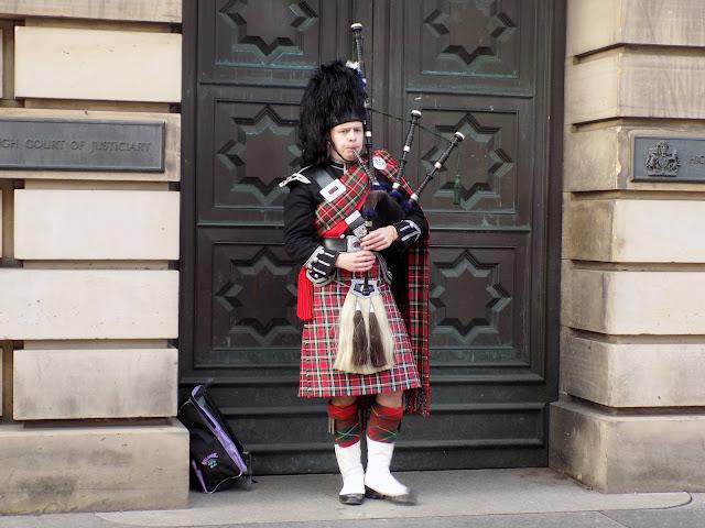 Scottish man in kilt playing bagpipes in Edinburgh